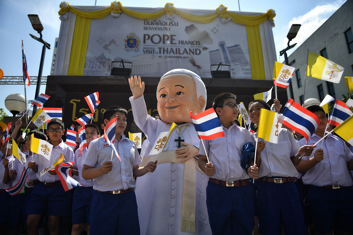 Catholic schoolchildren wait for Pope Francis to arrive outside of the Apostolic Nunciature of the Holy See in Bangkok on Nov. 20. LILLIAN SUWANRUMPHA/AFP via Getty Images