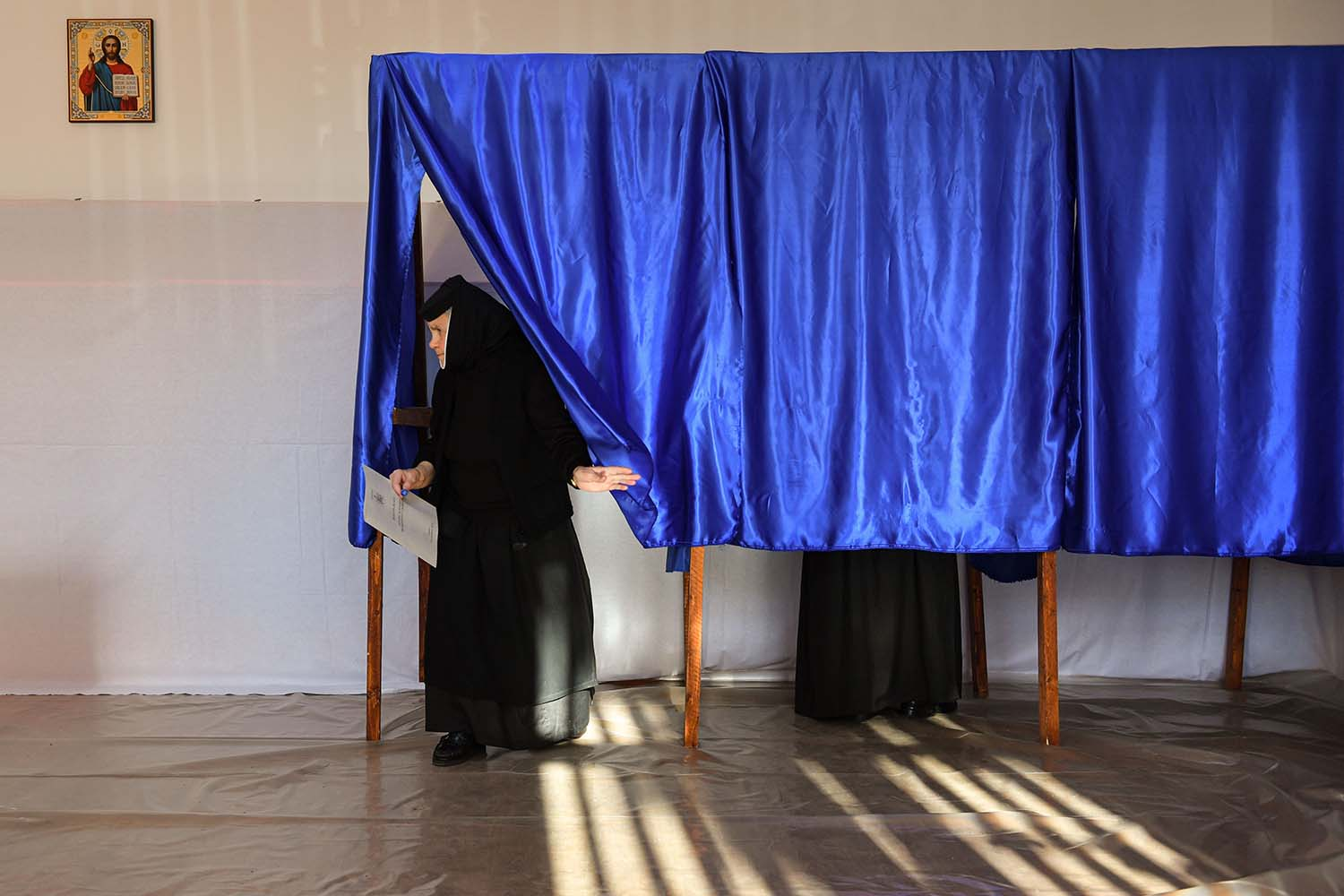 Orthodox nuns vote at a polling station in Branesti village in the first round of Romania's presidential elections on Nov. 10. DANIEL MIHAILESCU/AFP via Getty Images