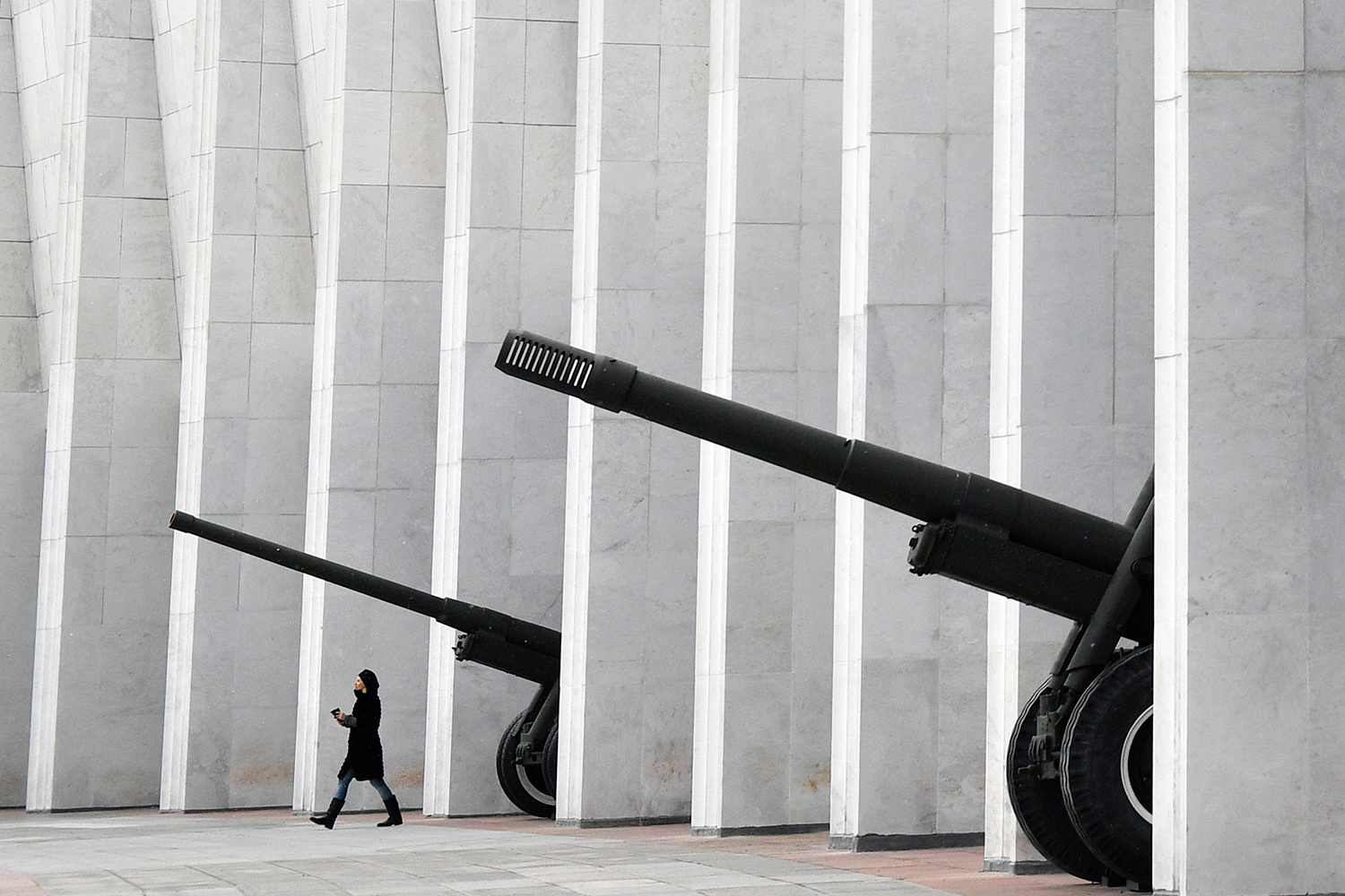 A woman walks past WWII-era artillery guns at the colonnade of the Museum of the Great Patriotic War at Poklonnaya Hill in Moscow on Oct. 31. ALEXANDER NEMENOV/AFP via Getty Images