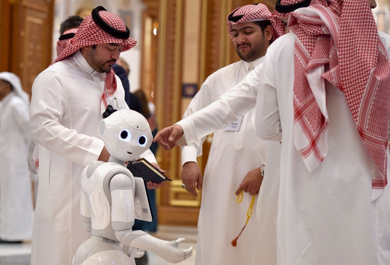 Delegates talk near a robot during the Future Investment Initiative forum in Riyadh, Saudi Arabia, on Oct. 30. FAYEZ NURELDINE/AFP via Getty Images