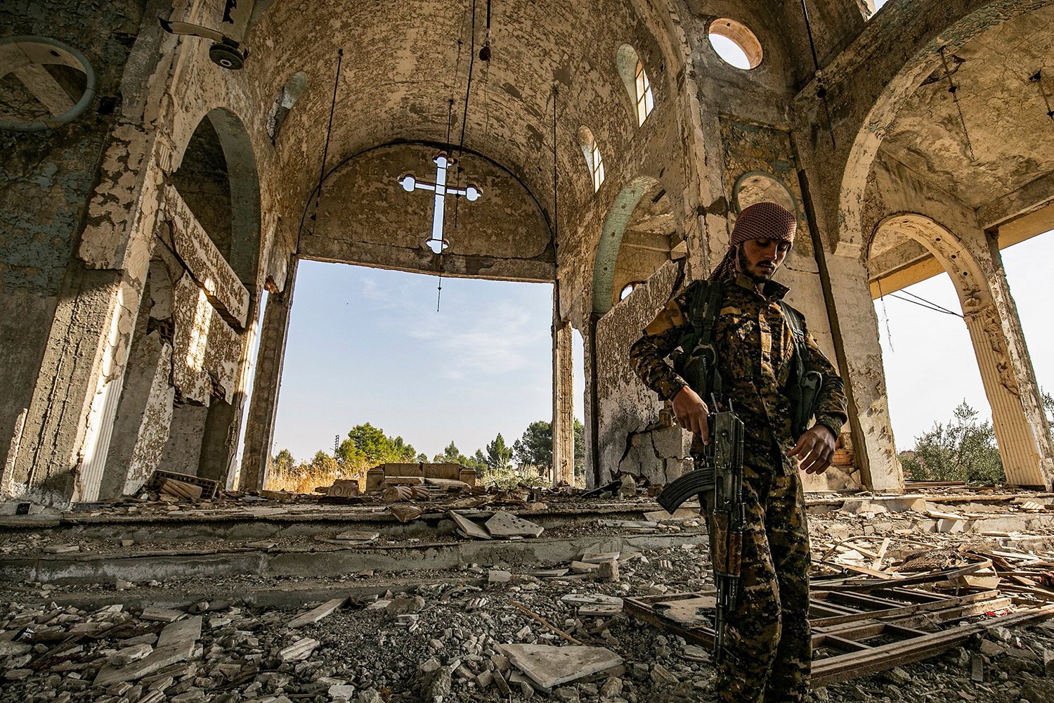 A member of the Khabour Guards (MNK) Assyrian Syrian militia, affiliated with the Syrian Democratic Forces (SDF), walks in the ruins of the Assyrian Church of the Virgin Mary, which was previously destroyed by Islamic State fighters, in Tal Nasri in Syria's northeastern Hasakah province on Nov. 15. DELIL SOULEIMAN/AFP via Getty Images