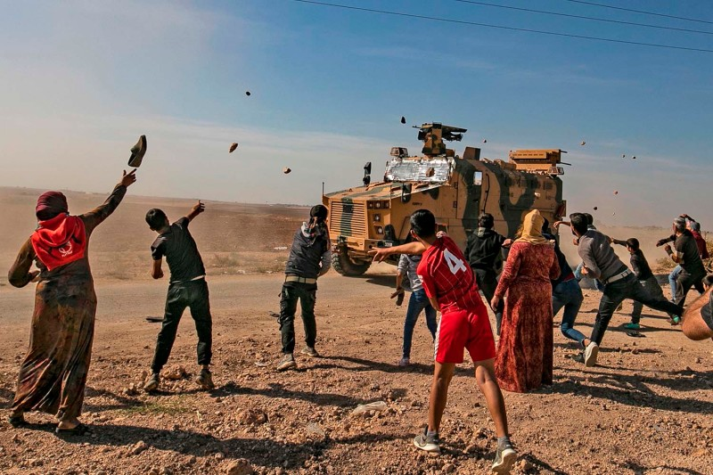 Syrians throw stones towards Turkish military vehicles during a Turkish-Russian army patrol near the town of Darbasiyah in Syria's northeastern Hasakeh province along the border with Turkey on Nov. 11. DELIL SOULEIMAN/AFP via Getty Images