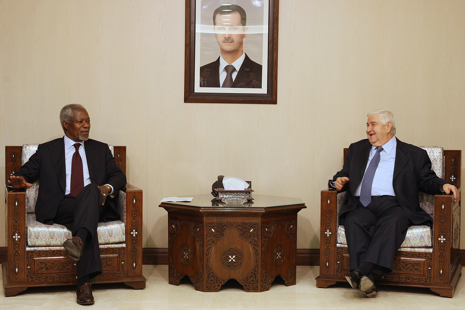 Former U.N. General-Secretary Kofi Annan meets with Syrian Foreign Minister Walid Muallem under a portrait of Syrian President Bashar al-Assad in Damascus on May 28, 2012.
