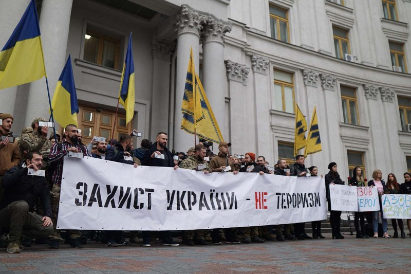 "Members of the Azov movement protest in front of Ukraine's Ministry of Foreign Affairs in Kyiv on Oct. 28 holding a banner that says ""Defense of Ukraine Is Not Terrorism!"""