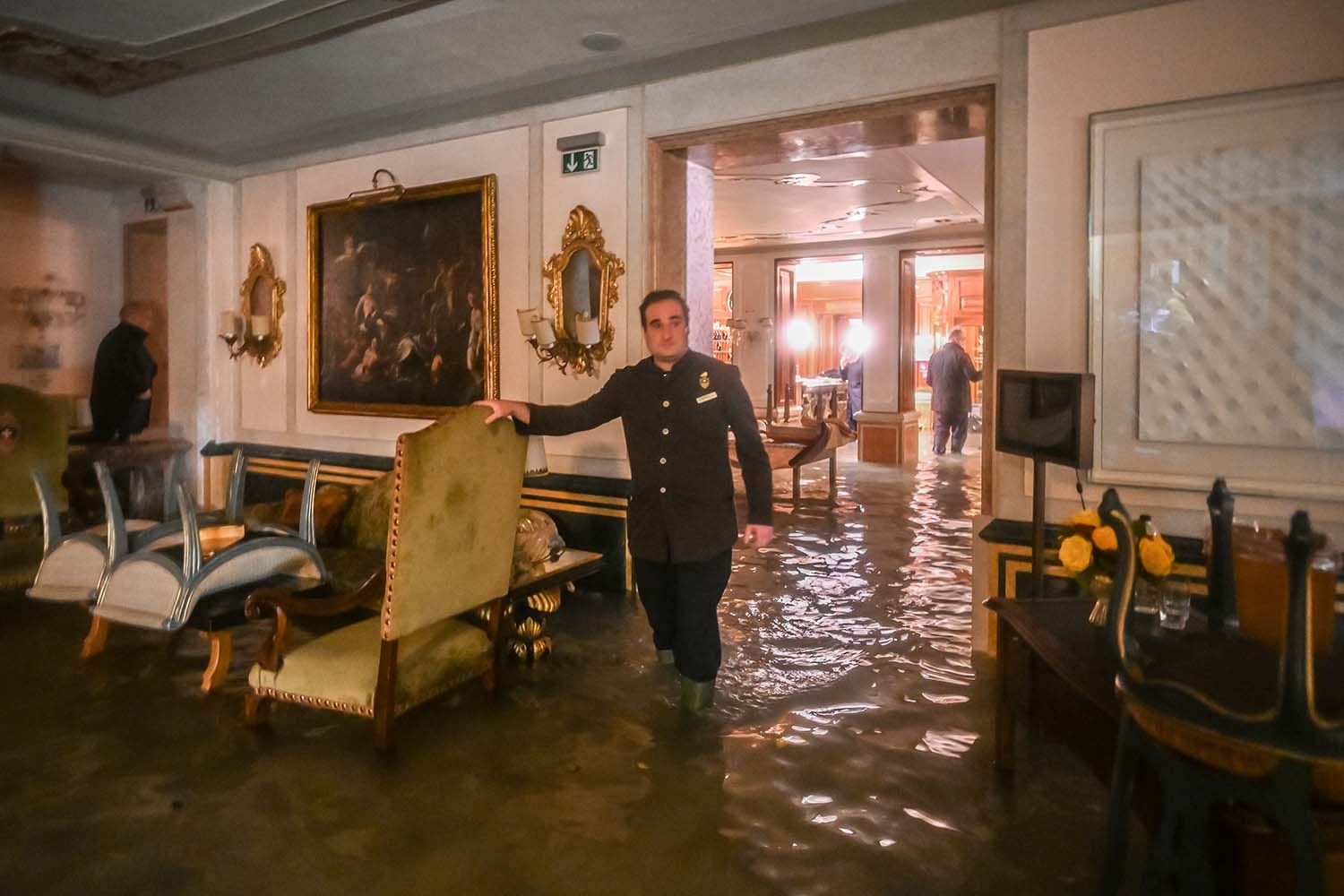 A man wades through a room in the flooded Gritti Palace during an exceptional Alta Acqua high tide in Venice on Nov. 12. MARCO BERTORELLO/AFP via Getty Images