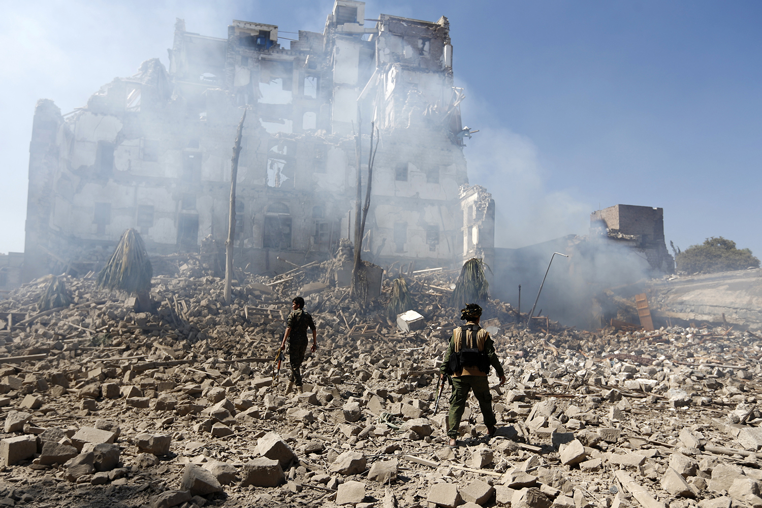 Huthi rebel fighters inspect the damage after a reported air strike carried out by the Saudi-led coalition targeted the presidential palace in the Yemeni capital Sanaa on Dec. 5, 2017.