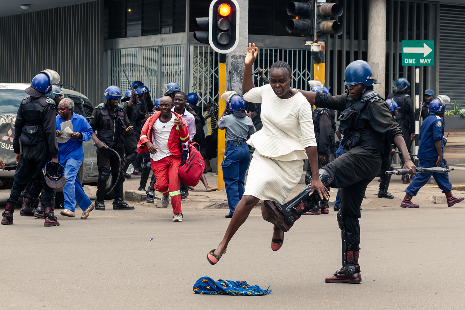 A Zimbabwe police officer tackles a woman with his boot as police disperse a crowd gathered to hear an address by Nelson Chamisa, the leader of the Movement for Democratic Change at Morgan Tsvangirai House, the party headquarters, in Harare on Nov. 20. JEKESAI NJIKIZANA/AFP via Getty Images