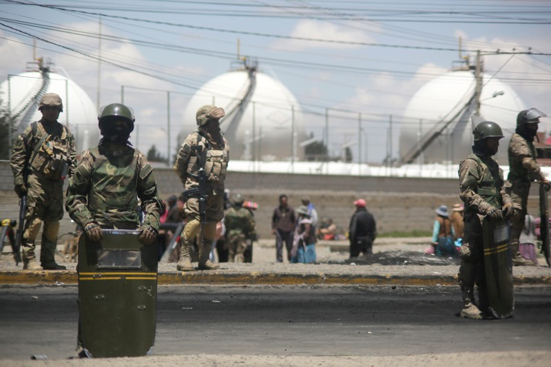 Military officers stand guard in front of the Senkata fuel plant as supporters of Evo Morales block the road on Nov. 20 in El Alto, Bolivia.