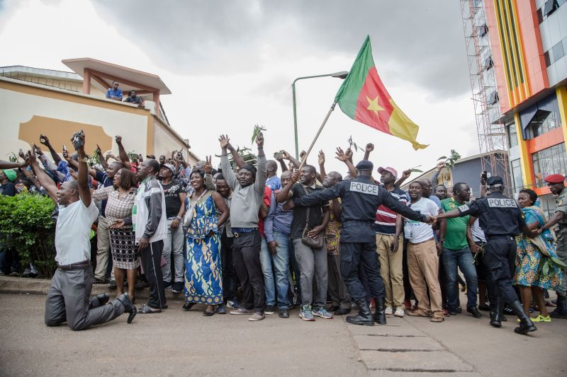 Hundreds of supporters raise their arms and wave the national flag while waiting to greet the Cameroonian opposition leader Maurice Kamto in Yaoundé on Oct. 5, the day of his release from prison.