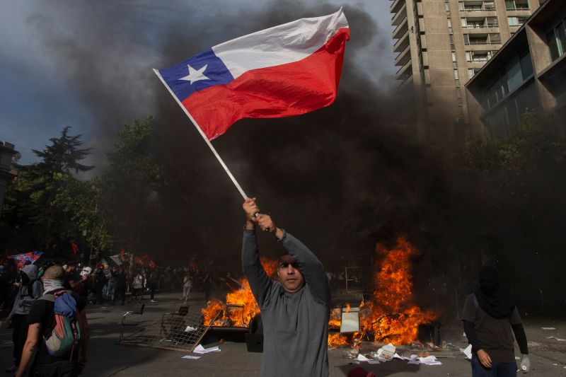 A demonstrator waves a Chilean flag at a barricade during a protest against the government's economic policies in Santiago on Oct. 29.