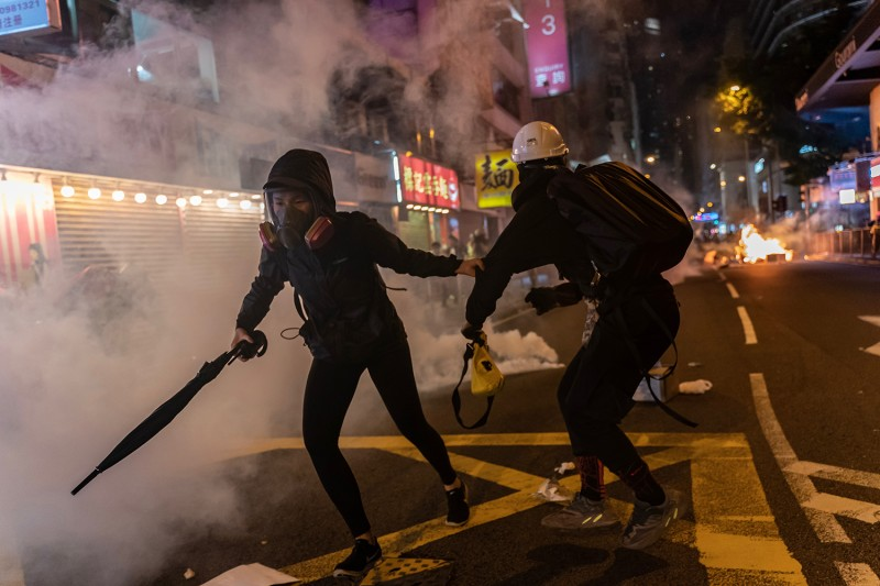 Pro-democracy protesters react as police fire tear gas on Nov. 2 in Hong Kong.