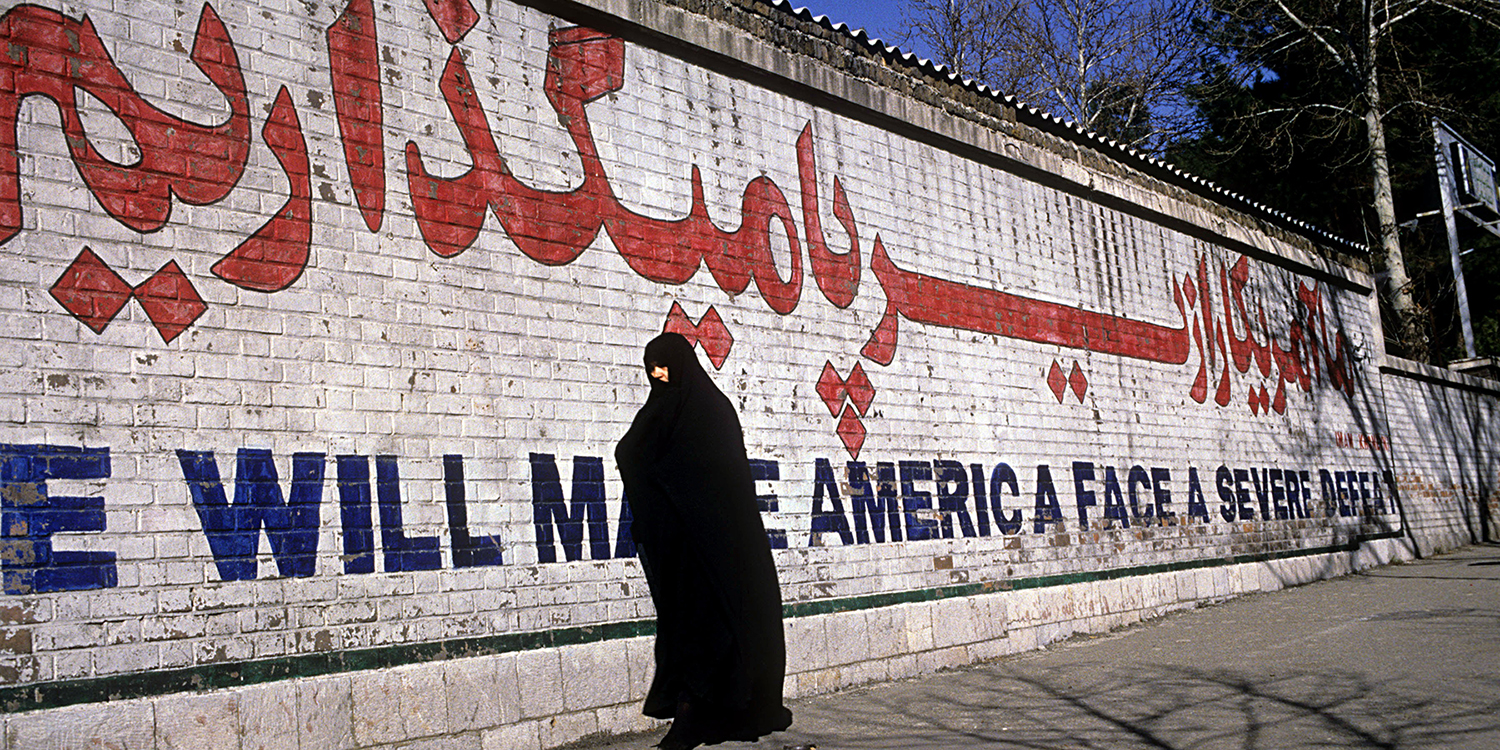 "A woman passes a mural featuring a quote by Ayatollah Khomeini, ""We will make America face a severe defeat,"" in Tehran on April 11, 1996."