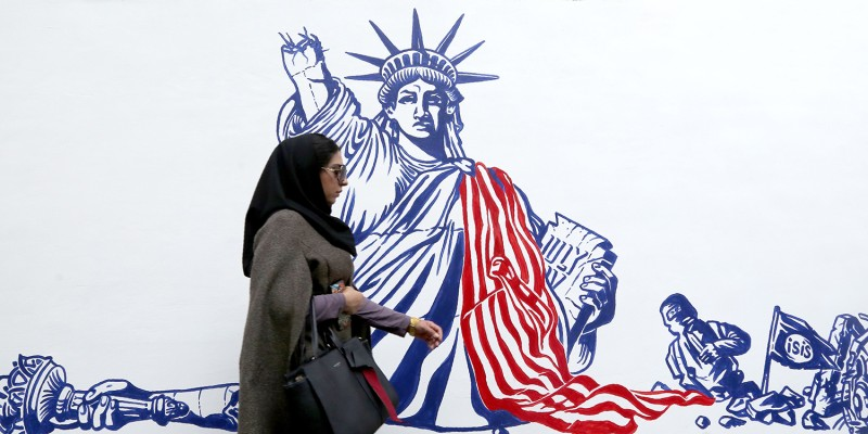 An Iranian woman walks past a new mural painted on the walls of the former U.S. Embassy in Tehran