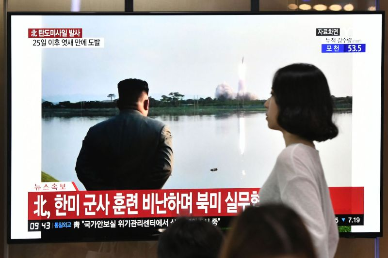 A woman in Seoul, South Korea walks past a television news screen showing file footage of North Korean leader Kim Jong Un watching a missile launch on July 31, 2019.