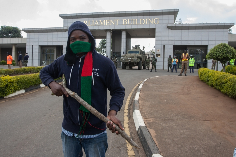 A protester holds a stick in front of Malawi Defense Force soldiers at the entrance of the Malawian parliament during a demonstration by opposition supporters against the re-election of the president, which protesters say was due to fraud, on July 4 in Lilongwe, Malawi.