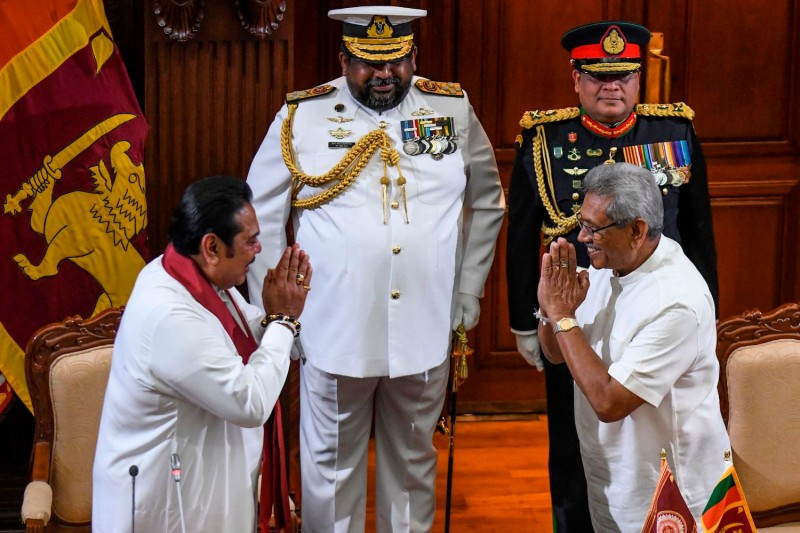 Former President Mahinda Rajapaksa (L) gestures after taking his oath as the country's new prime minister towards his brother, the newly-elected President Gotabaya Rajapaksa (R), during a ceremony in Colombo on Nov. 21.