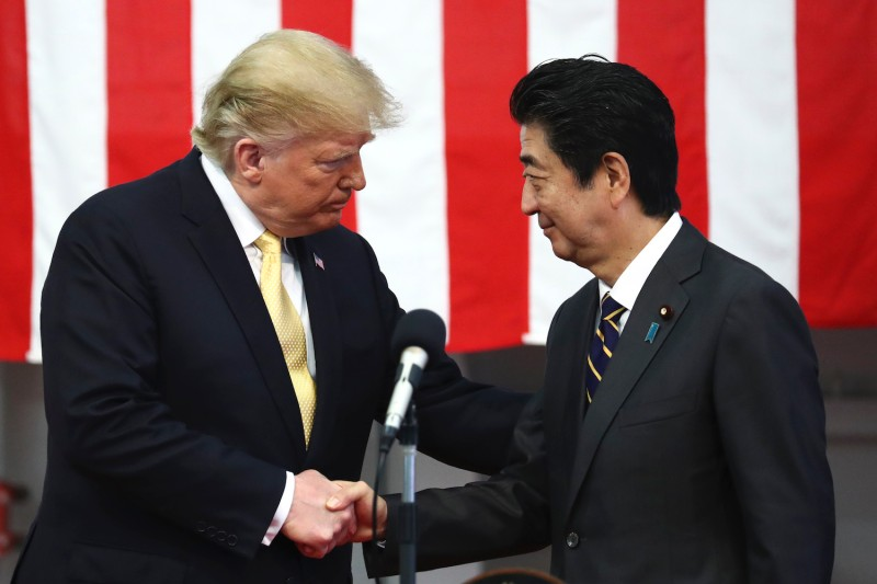 U.S. President Donald Trump shakes hands with Japanese Prime Minister Shinzo Abe while speaking to Japanese and U.S. troops aboard a helicopter carrier on May 28 in Yokosuka, Japan.