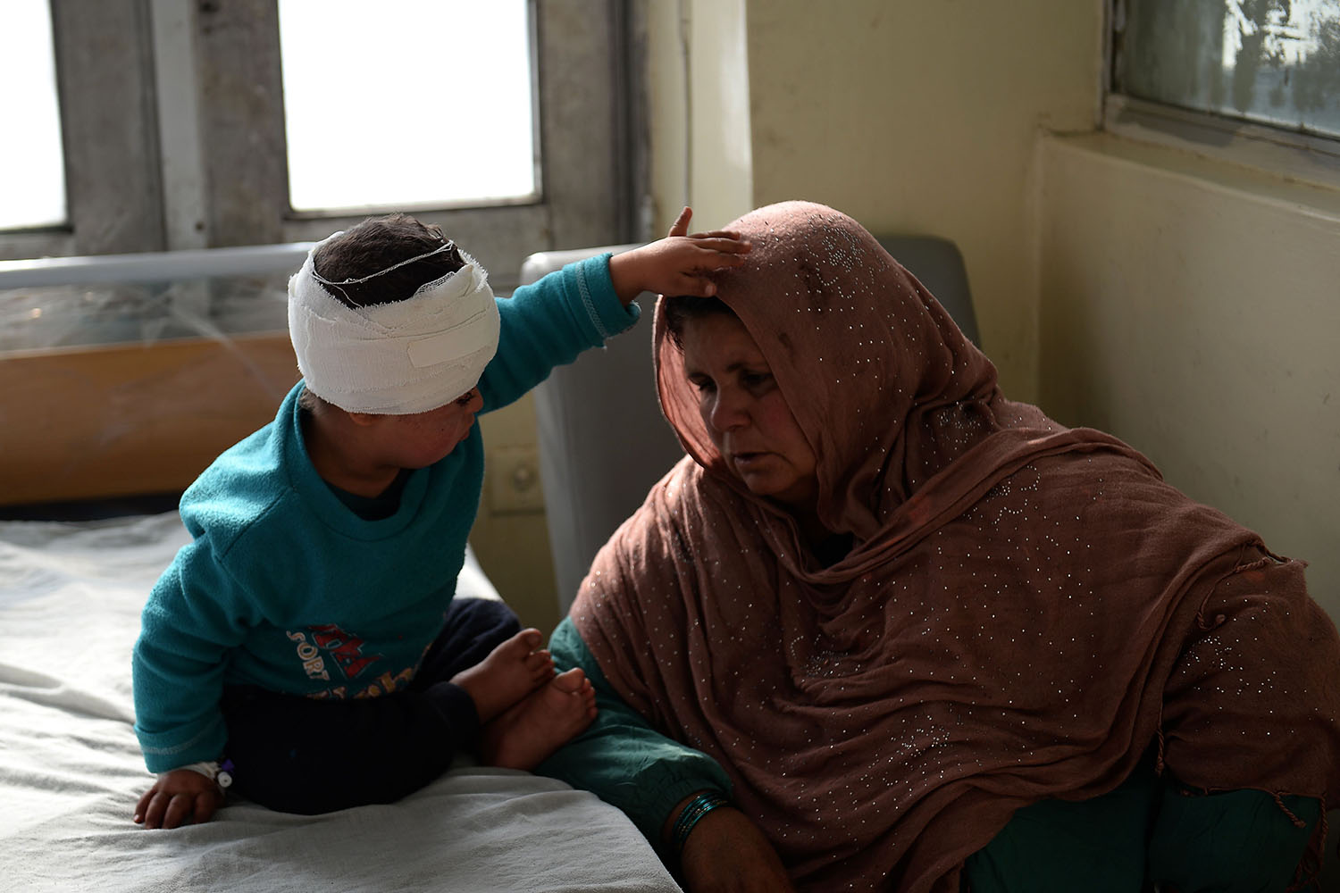 An Afghan woman sits next to a wounded child after receiving treatment at Indira Gandhi Children's Hospital following a powerful truck bomb attack in Kabul on Jan. 15. The Taliban claimed responsibility for the attack that killed at least four people and wounded more than 100. SHAKIB RAHMANI/AFP/Getty Images