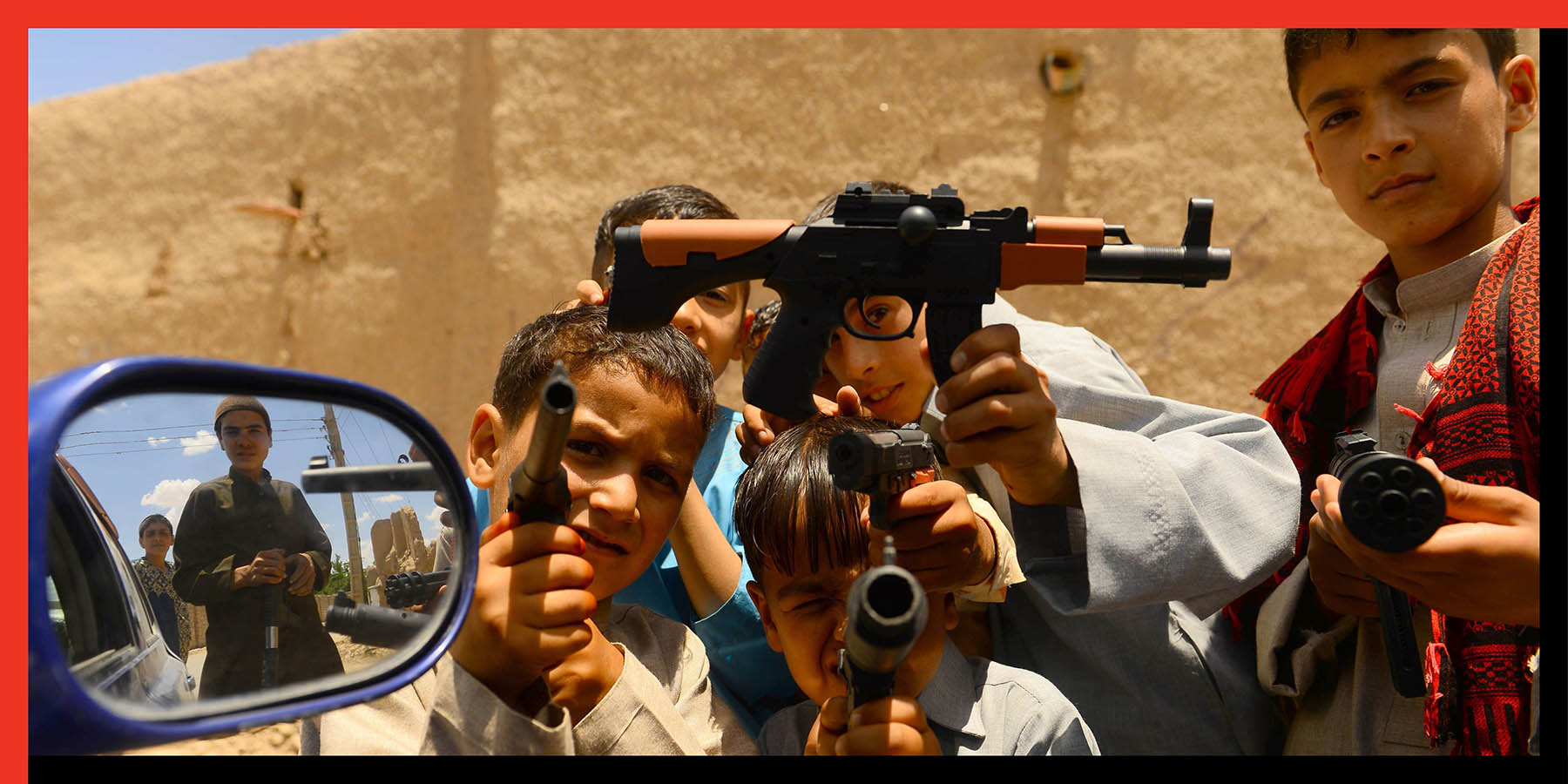 Afghan boys play with plastic guns in Herat, Afghanistan, on June 4.