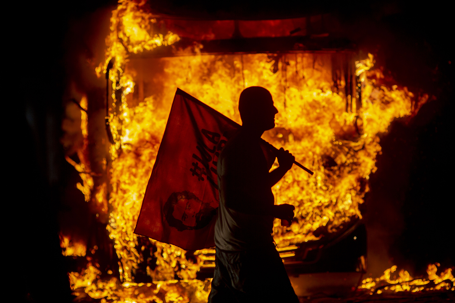 BRAZIL | A man holds a flag depicting former Brazilian President Luis Inacio Lula da Silva past a bus in flames during a protest organized by the National Students Union in Rio de Janeiro on May 15. Students and teachers from hundreds of universities and colleges began a nationwide demonstration in defense of education following a raft of budget cuts announced by President Jair Bolsonaro's government. MAURO PIMENTEL/AFP/Getty Images