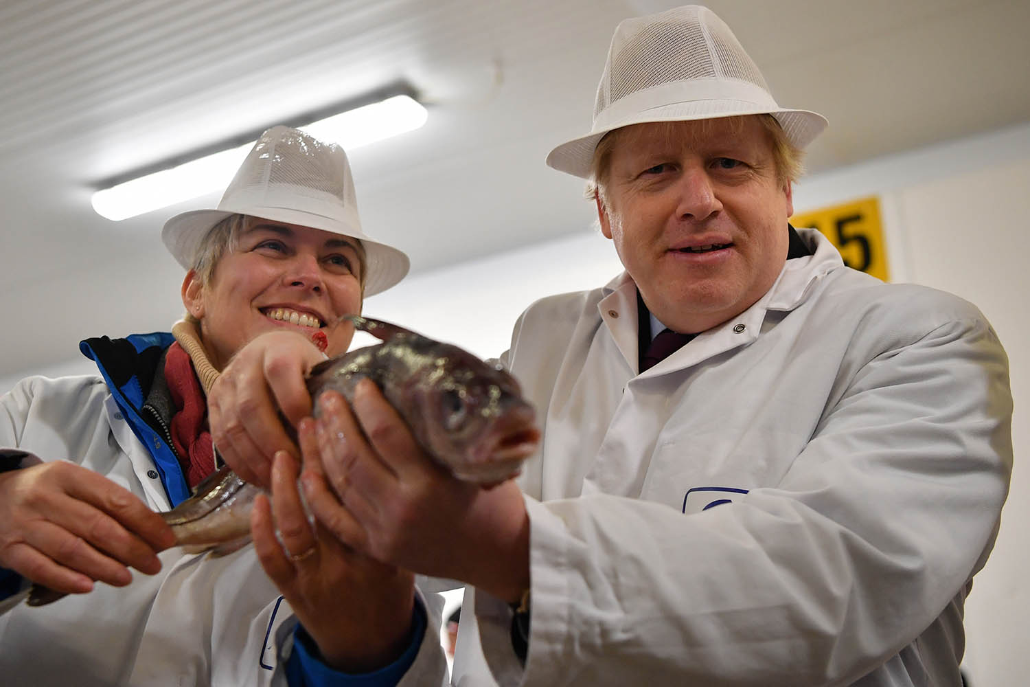 Johnson holds a fish with Lia Nici, Conservative candidate for Great Grimsby, during a campaign visit to Grimsby Fish Market on Dec. 9.