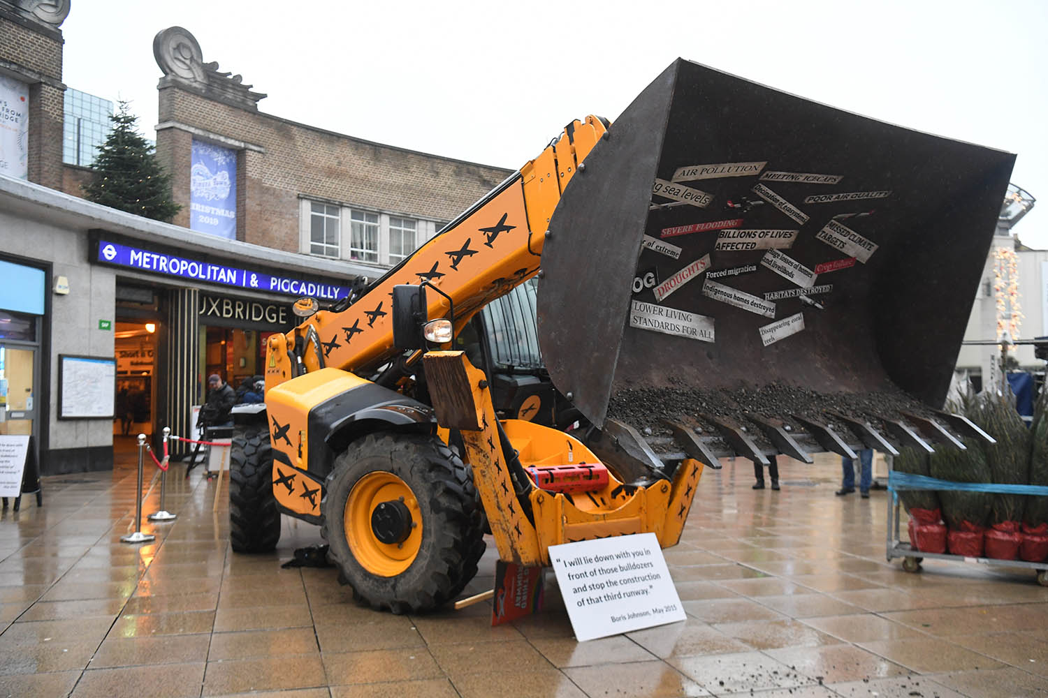 A bulldozer placed by Greenpeace protesters outside Uxbridge tube station in Johnson's constituency on Nov. 26. The display includes a placard with Johnson's quote pledging to stop the expansion of Heathrow airport.