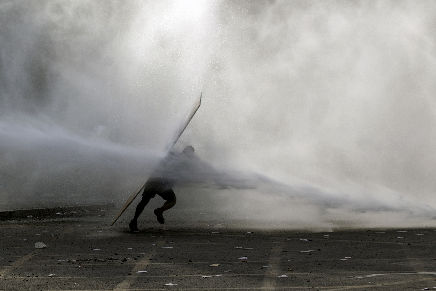 CHILE | A demonstrator is hit by riot police water cannon spray during a protest against the government in Santiago on Nov. 18. CLAUDIO REYES/AFP via Getty Images