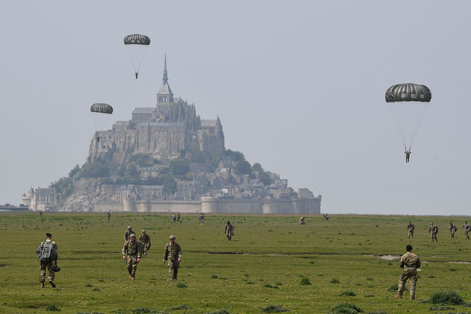 U.S. paratroopers walk back after jumping over Le Mont-Saint-Michel, northwestern France on May 18, less than three weeks before the 75th anniversary of the D-Day landings. DAMIEN MEYER/AFP/Getty Images