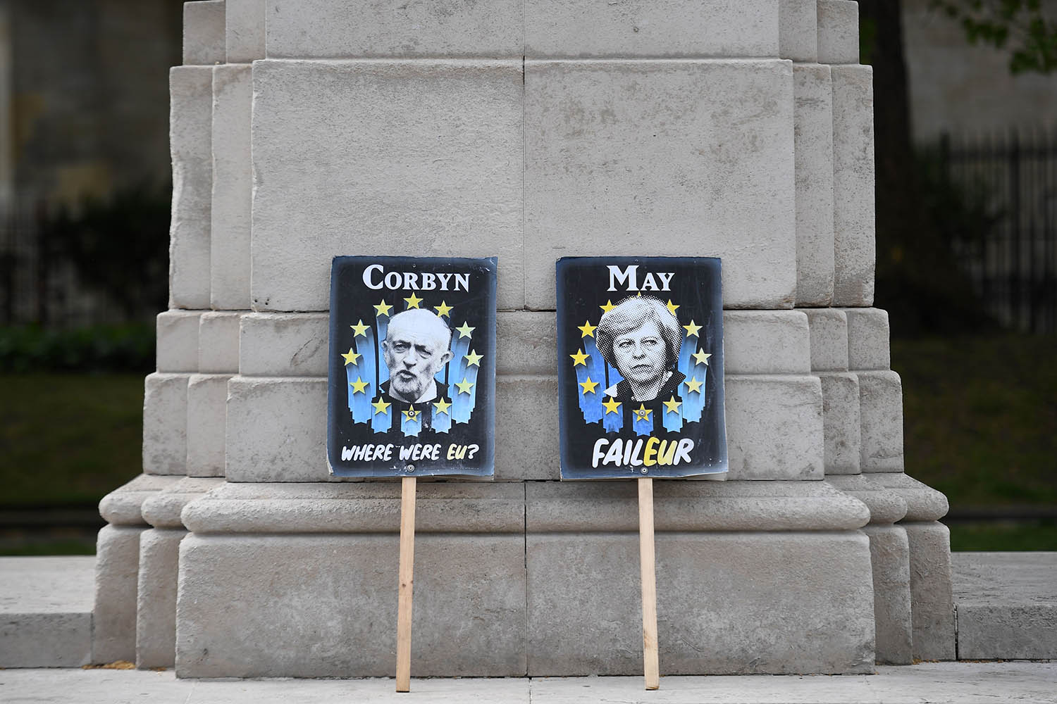 Placards featuring Britain's Labour party leader Jeremy Corbyn and Britain's then-Prime Minister Theresa May in the colours of the European Union lean against a pillar near the Houses of Parliament in London on April 25.