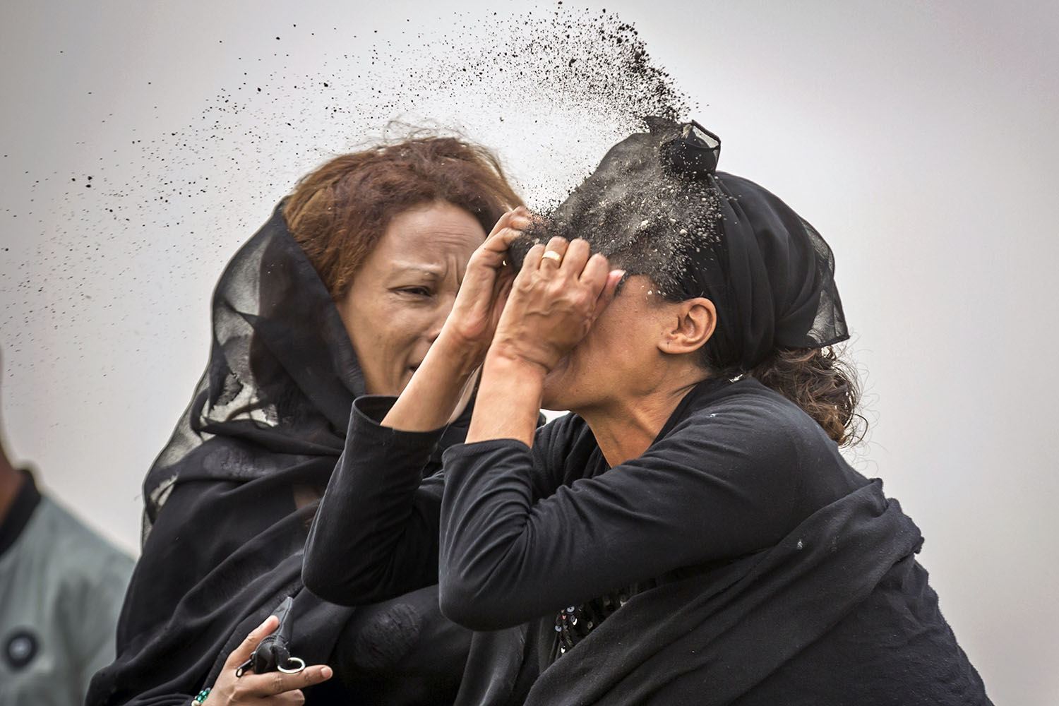 A relative of a plane crash victim throws dirt in her face as she mourns on March 14 at the site near Bishoftu where the Ethiopian Airlines Boeing 737 Max 8 crashed shortly after takeoff  killing all 157 on board. Mulugeta Ayene/AP
