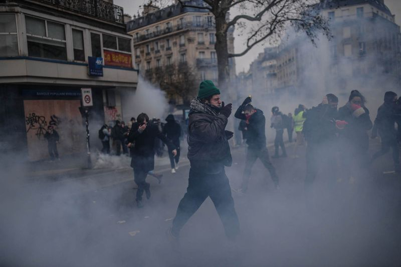 People run away from tear gas during a national general strike in Paris on Dec. 5. BULENT KILIC/AFP via Getty Images