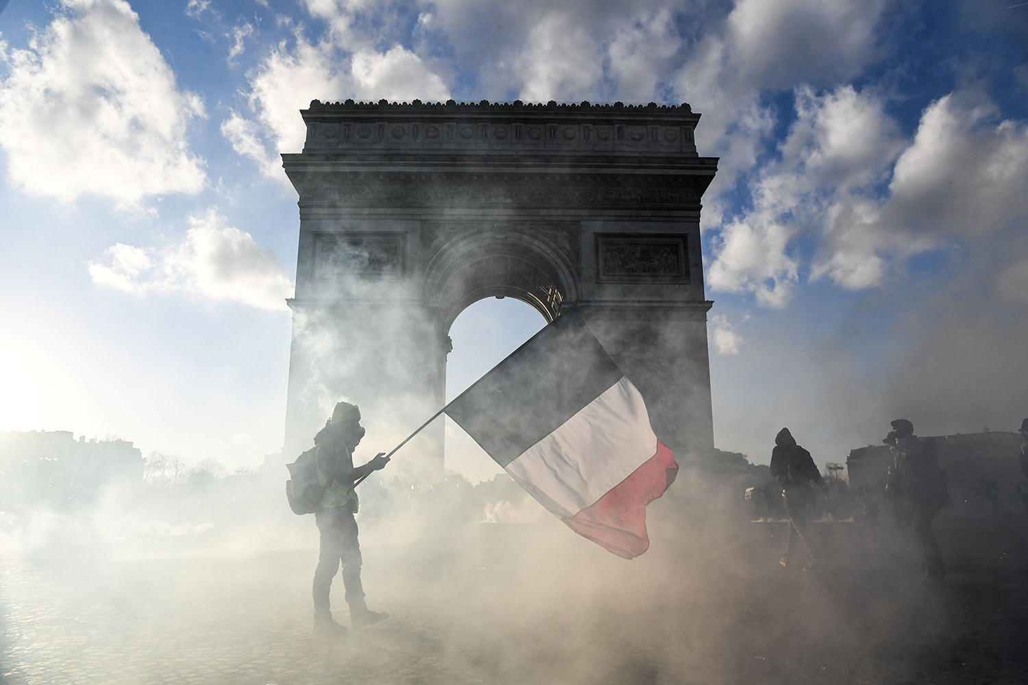 FRANCE | A protester holds a national flag as he walks among tear gas smoke past the Arc de Triomphe during clashes between Yellow Vest protesters and riot police in Paris on March 16. ALAIN JOCARD/AFP via Getty Images