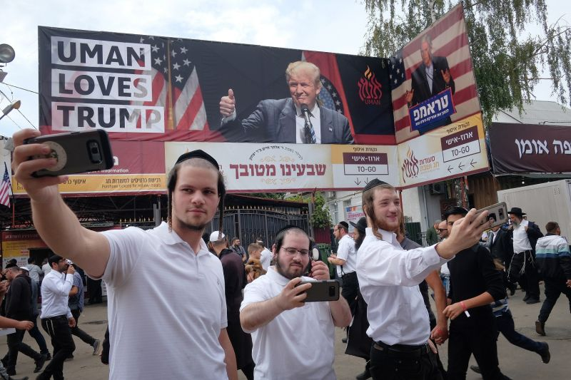 "Hasidic Jews shoot selfies under a banner that reads: ""Uman Loves Trump"", prior to the annual Rosh Hashanah celebration on September 9, 2018 in Uman, Ukraine."