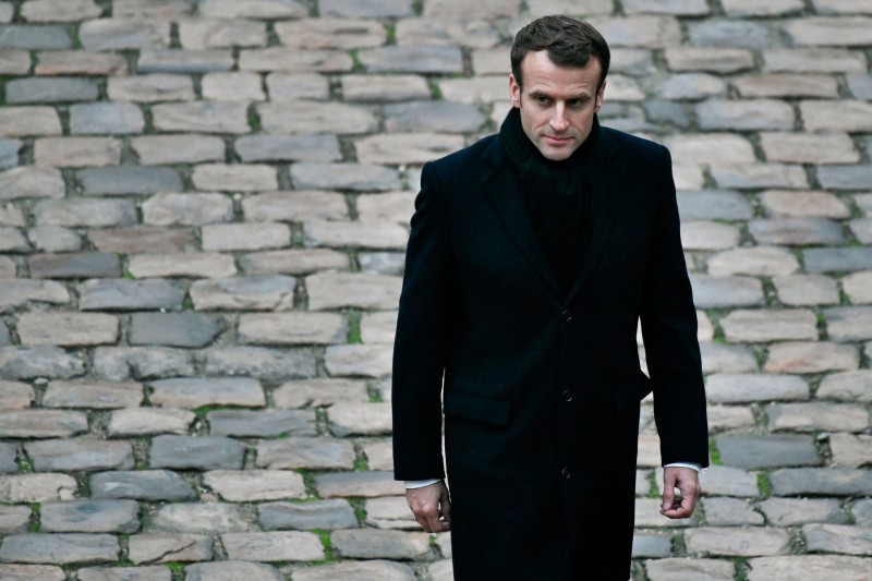 """French President Emmanuel Macron walks during a """"Prise d'armes"""" military ceremony at the Invalides in Paris, on November 26, 2018."""