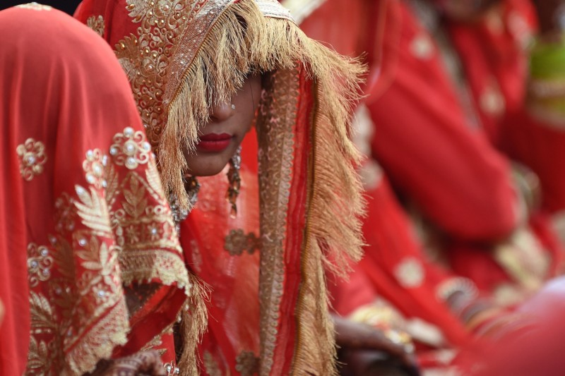 An Indian bride looks on as she and others participate in a mass marriage in Ahmedabad on Dec. 3, 2018.