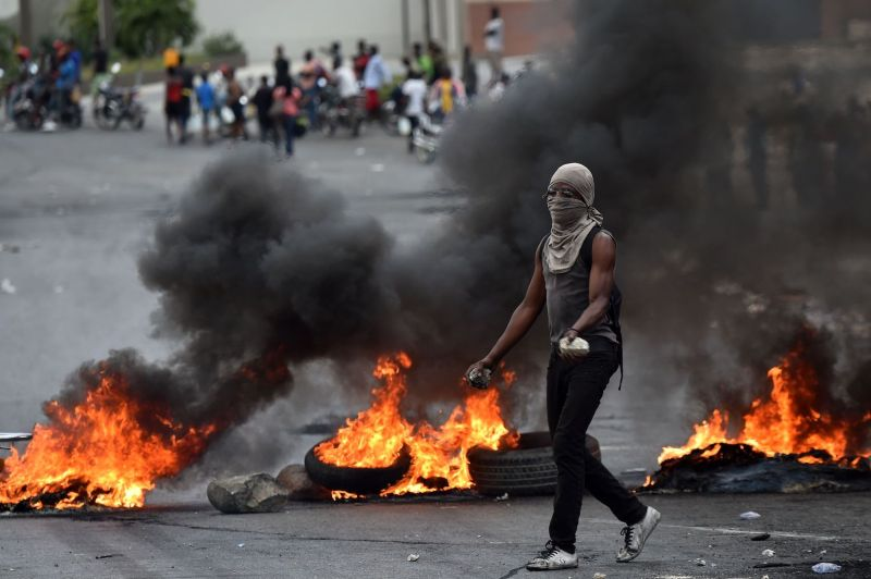 A protester walks past barricades in Haiti.