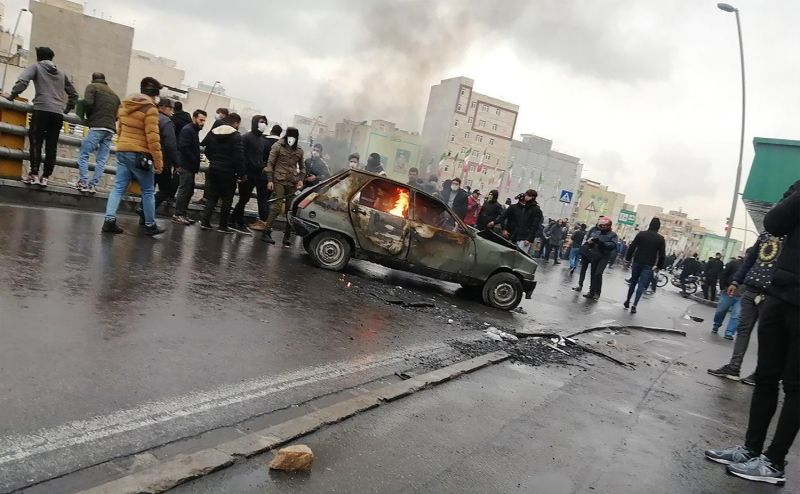 Iranian rotesters gather around a burning car during a demonstration against an increase in gasoline prices in Tehran, on Nov. 16.