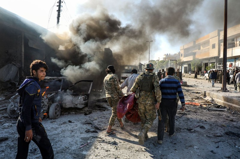 Pro-Turkish Syrian fighters carry away remains of the victims of a car bomb explosion at the industrial zone in the northern Syrian town of Tal Abyad
