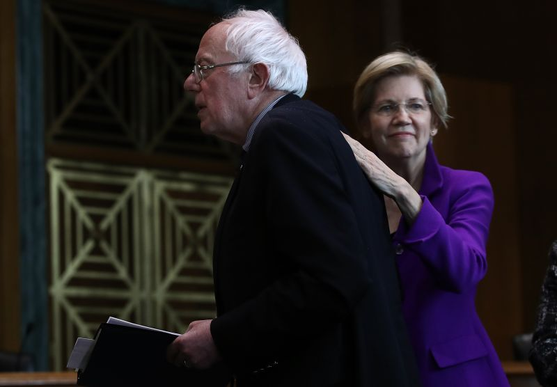 U.S. Sen. Elizabeth Warren, right, pats Sen. Bernie Sanders on the back
