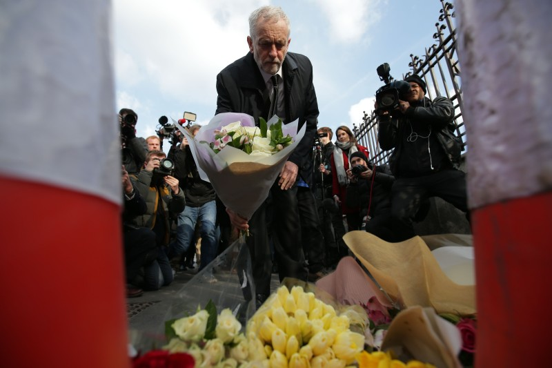 British Opposition Labour Party leader Jeremy Corbyn lays a bunch of flowers at the end of Westminster Bridge by the Houses of Parliament in central London on March 23, 2017.
