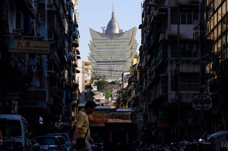 A pedestrian walks in a residential neighborhood in front of a view of the Grand Lisboa casino resort in Macao on Aug. 29, 2017.