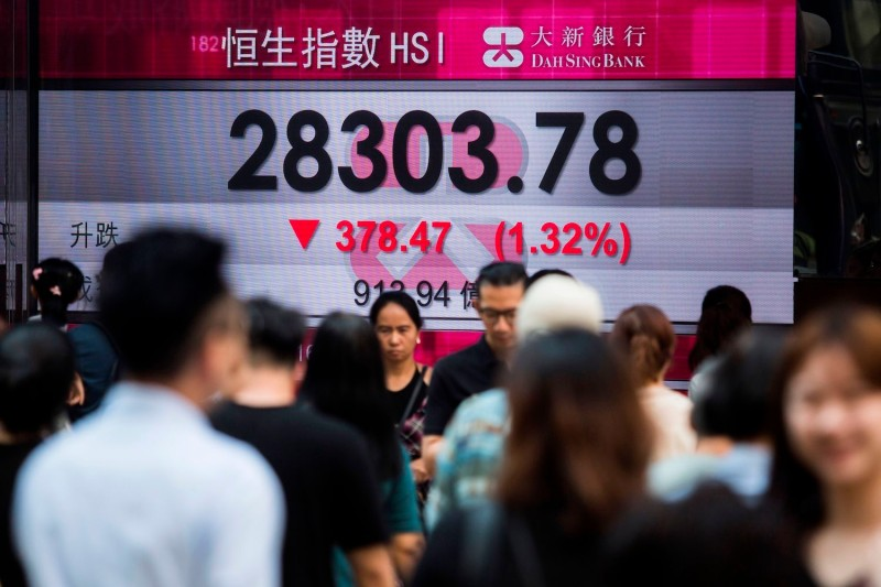 Pedestrians walk past an electronic billboard displaying the Hang Seng Index in negative territory on the Hong Kong Stock Exchange