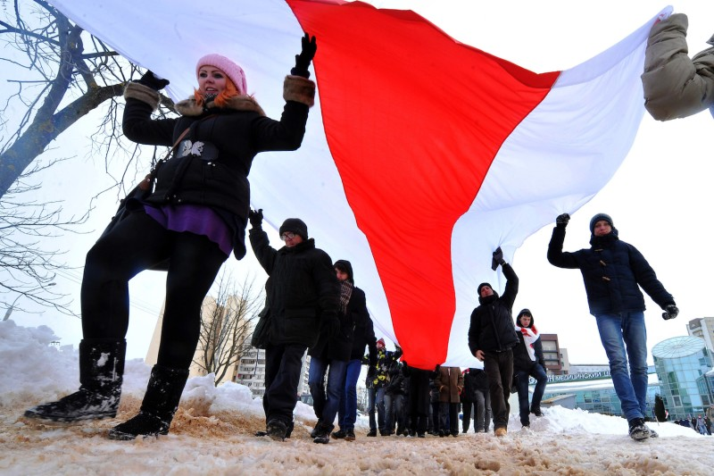 Belarusian opposition protesters carry a giant flag during a rally in Minsk on March 24, 2013.