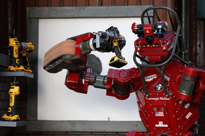 Team Tartan Rescue's CHIMP (CMU Highly Intelligent Mobile Platform) robot uses a hand-held power tool during the Defense Advanced Research Projects Agency (DARPA) Robotics Challenge in California on June 6, 2015.