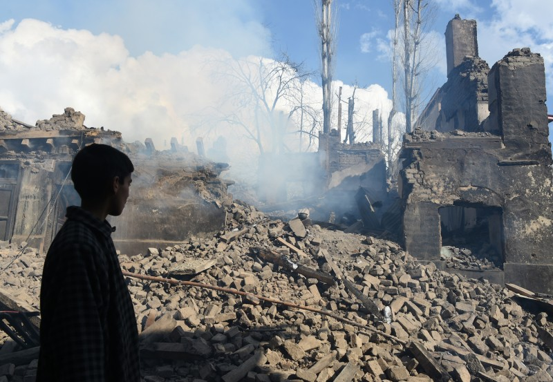 A young Kashmiri villager looks at the remains of a house destroyed during a deadly gun battle between militants and Indian government forces south of Srinagar, on March 5, 2019.