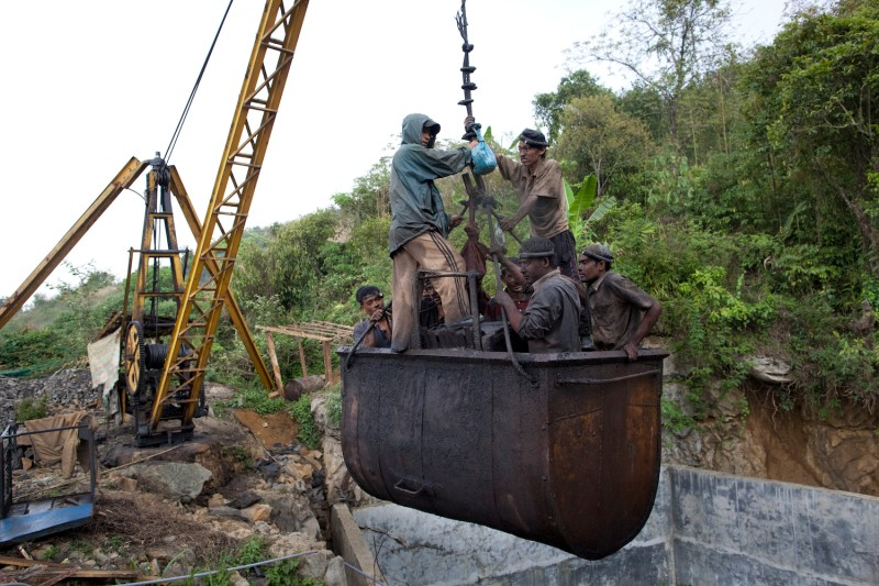 A crane lifts miners out of the shaft of a coal mine as workers break for lunch near the village of Latyrke near Lad Rymbai, in the district of East Jaintia Hills in Meghalaya, India, on April 13, 2011.