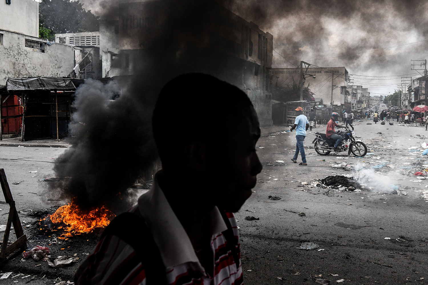 HAITI | A man walks past burning tires during a protest against fuel shortages and to demand the resignation of President Jovenel Moise, in Port-au-Prince on Sept. 25. CHANDAN KHANNA/AFP/Getty Images