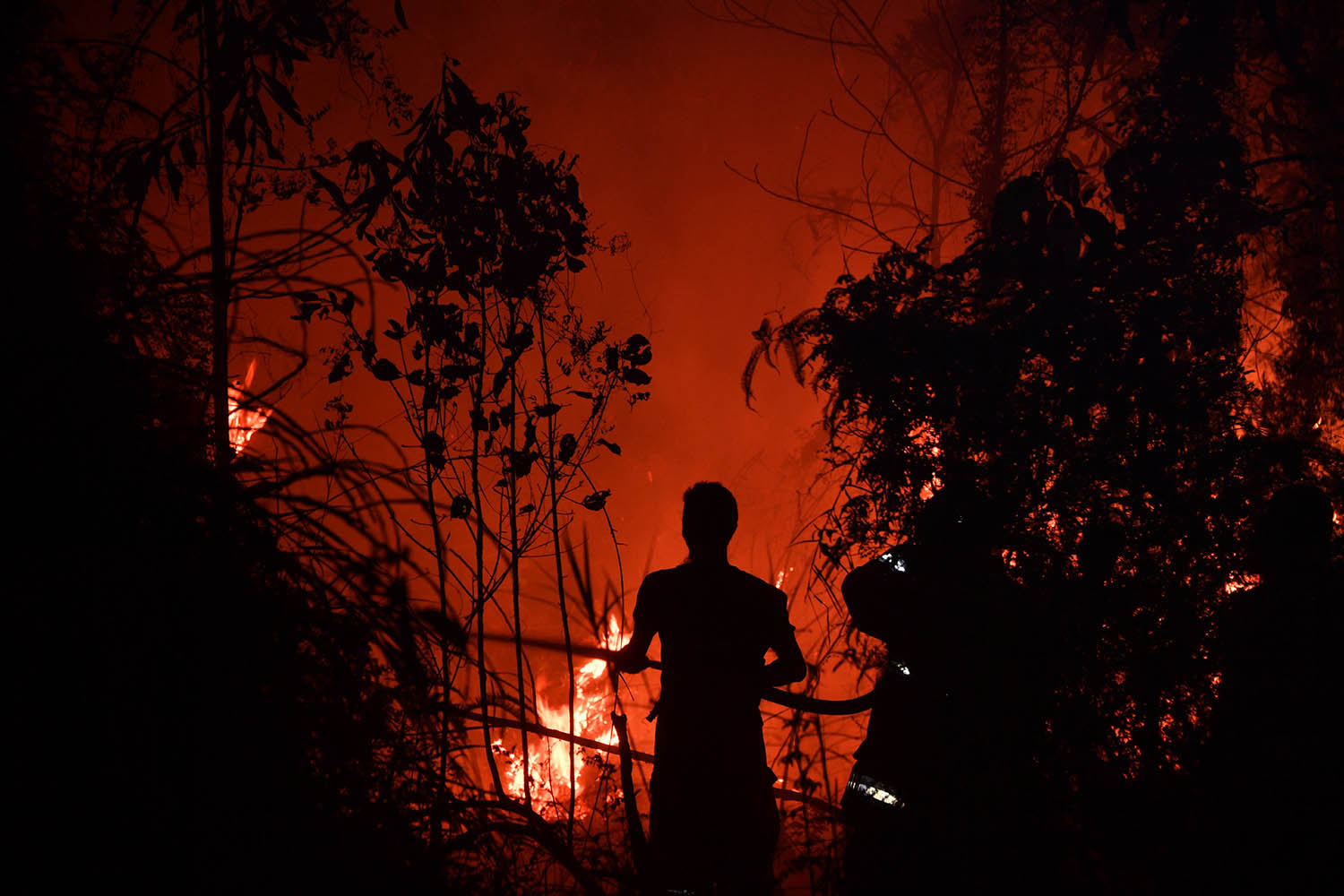 Indonesian firefighters extinguish a fire in Pekanbaru, Riau province, on Sept. 13 as the number of blazes in Indonesia's rainforests jumped sharply, adding to concerns about the impact of wildfire outbreaks worldwide on global warming.