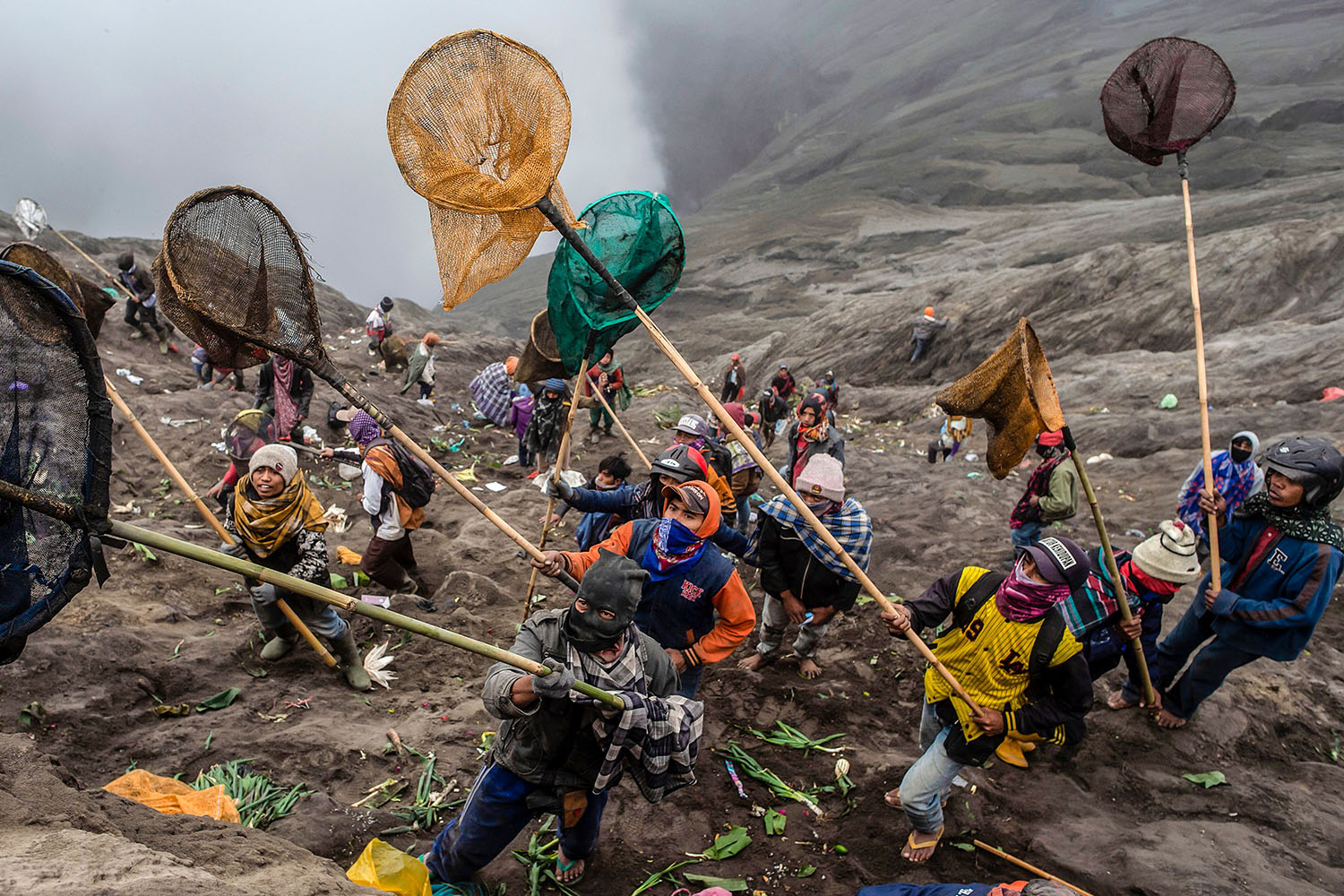 People try to catch offerings thrown off the summit of the active Mount Bromo volcano by Tengger tribe members and local tourists in Probolinggo, East Java province, Indonesia, as part of the Yadnya Kasada Festival on July 18. During the festival, the Tenggerese climb the volcano and seek blessings of the main deity by presenting offerings of rice, fruit, livestock, and other items. JUNI KRISWANTO/AFP/Getty Images