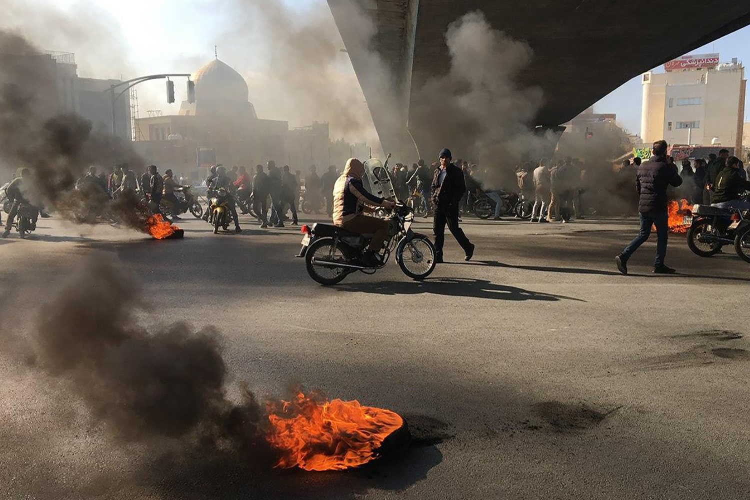 IRAN | Protesters rally amid burning tires during a demonstration against an increase in gasoline prices in the central city of Isfahan on Nov. 16. -/AFP via Getty Images